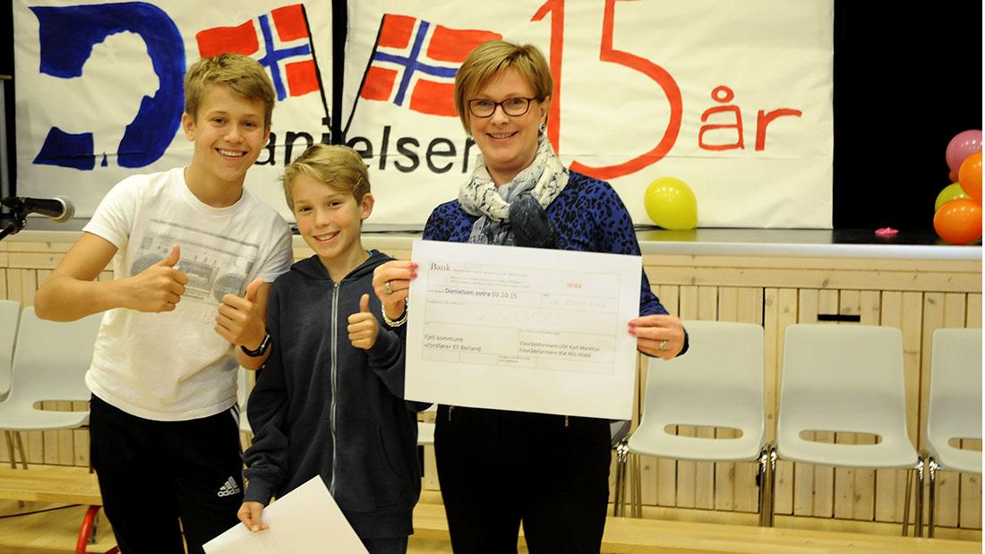 Elevrådslederne Kjell Markhus i 10. klasse og Nils Hisdal i 7. klasse overrakte pengesjekken på 23.000 kroner til ordfører i Fjell kommune, Eli Berland